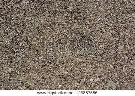 Abstract background of close up asphalt dark black texture with rock uneven surface on urban empty street outdoor