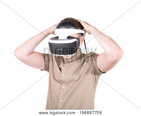 A young man action in virtual reality helmet, isolated on a white background. VR Glasses. A guy wearing virtual reality goggles. Professional audio equipment.