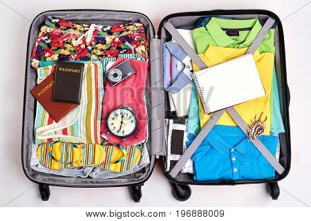 Ready suitcase for travelling. Opened suitcase full of clothing.