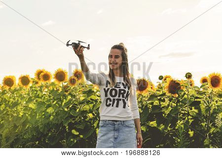 Beautiful woman is holding a mini dron on the background of a field sunflowers. Dron is preparing to take off.