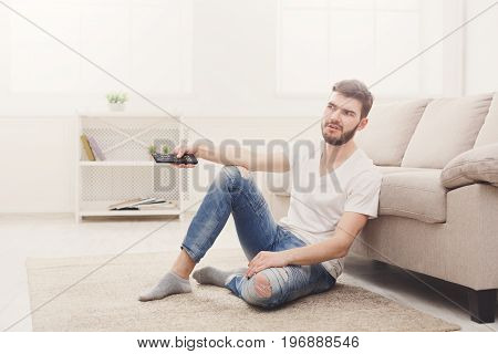 Dissatisfied young man sitting on the floor watching tv using remote controller in living room, copy space