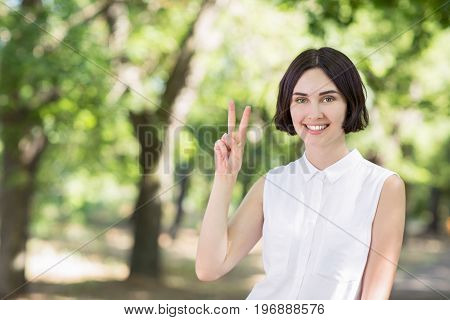 Close-up portrait of European girl in casual clothes with an optimistic smile, showing victory sign with right hand, looking friendly on bright green background. A cute lady is giving peace gesture.