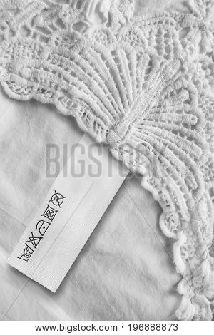 Washing instructions clothes label on white linen as a background