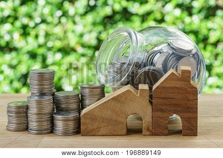 wooden miniature house with stack of coins and coins in glass jar with green bokeh background as financial saving or mortgage concept.