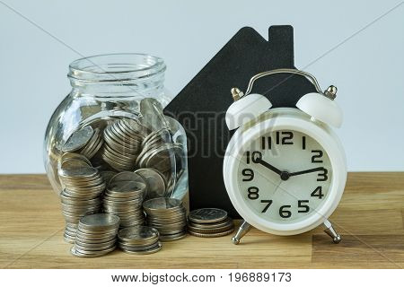 white alarm clock and stack of coins and coins in glass jar with paper house on wooden table as financial saving target concept.
