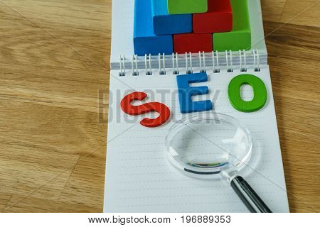 SEO Search engine optimization concept as colorful alphabet abbreviation SEO on magnifying glass on note paper and wooden block as analysis chart on wooden table.