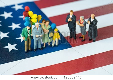 miniature people celebrate Independence day man giving speech with happy family holding balloons and United State national flag in the background.