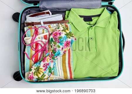 Beach accessories in open suitcase. Woman swimsuit in floral print.