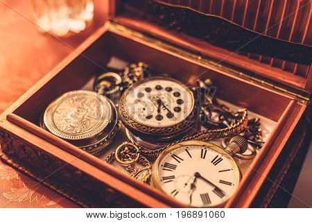 Ancient vintage pocket watch or clock in a wooden box, toned