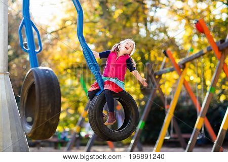 Kids on playground Children play in autumn park. Child on slide and swing on sunny fall day. Preschool or kindergarten yard. Daycare for young kid. Girl on play ground. Outdoor fun in autumn.