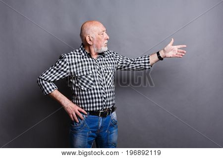 Confident senior man point away. Serious mature male gesturing with his hand aside, gray studio background, copy space