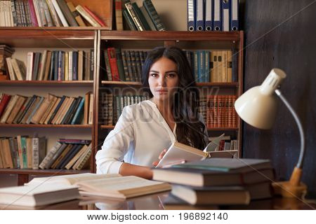 the girl sitting at the table reading a book is preparing for the exam