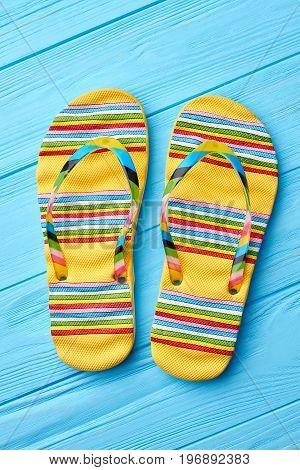 Summer fashion striped sandals. Colorful flip flops on blue background.