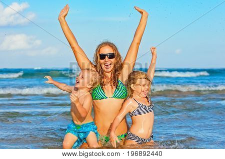Happy family lifestyle. Young mother with children jumping and splashing with fun in breaking waves. Summer travel water sport outdoor activities swimming lessons on tropical beach holiday with kids