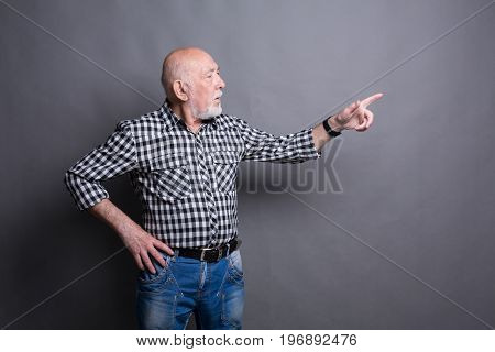 Confident senior man point away. Serious mature male gesturing with his finger aside, gray studio background, copy space