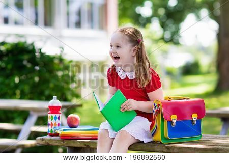 Child going back to school. Start of new school year after summer vacation. Little girl with backpack and books on first school day. Beginning of class. Education for kindergarten and preschool kids.