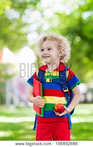 Child going back to school. Start of new school year after summer vacation. Little boy with backpack and books on first school day. Beginning of class. Education for kindergarten and preschool kids.
