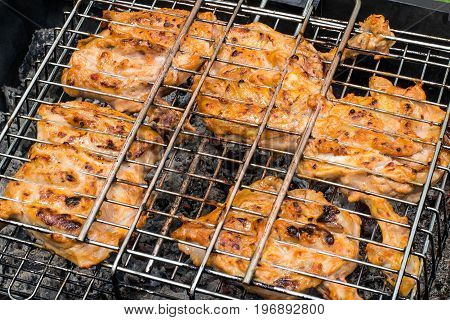 Popular dish of Turkish cuisine. Chicken chop on bone (pirzola) roasted on grill over hot coals during picnic in open air. Close-up