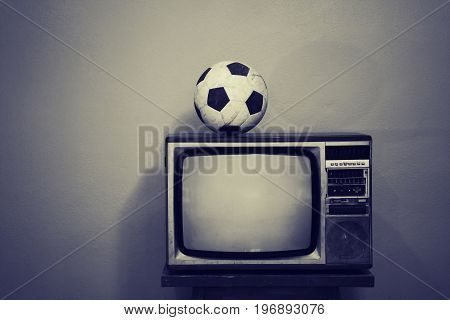 An old football on an old television, black and white toned.