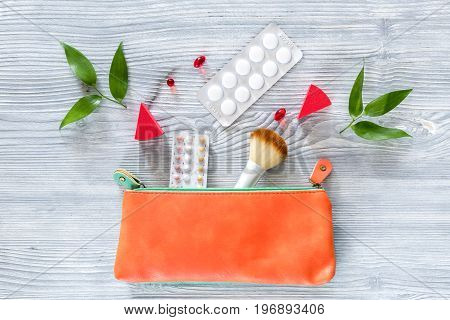 Beauty bag with cosmetics, contraceptives and pills on wooden table background top view.