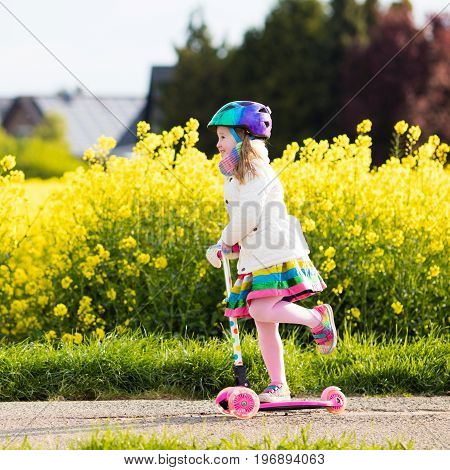 Child riding scooter on way back to school. Little girl playing outdoors learning to balance on kick board. Kids ride scooters in suburbs street. Preschooler in safe helmet on bike or roller.