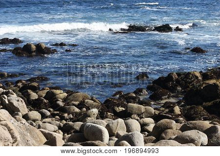 This is an image of the rocky sea shore of Pacific Grove, California taken on a clear sunny day.
