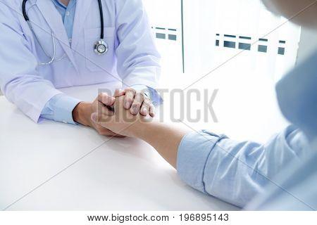 Hand Of Doctor Reassuring His Patient