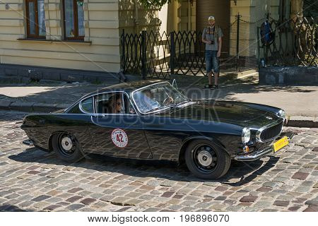 Lviv Ukraine - June 4 2017: Old retro car VOLVO P1800E with its owner and au unknown passengers taking participation in race Leopolis grand prix 2017 Ukraine.