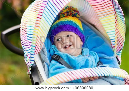 Baby in stroller on a walk in autumn park. Adorable little boy with knitted hat and jacket sitting in colorful pushchair under warm blanket. Fall outdoor fun for kids. Child in buggy on winter stroll.