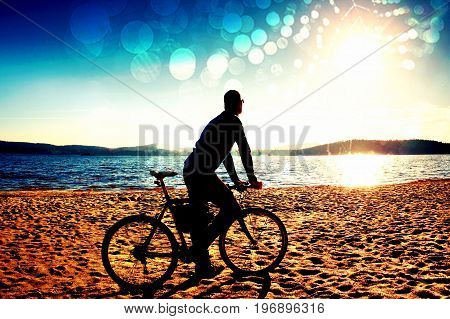 Film Grain. Young Man Cyclist Sit On Bike,  Blue Sky And Sunset Background On Beach. End Of Season A