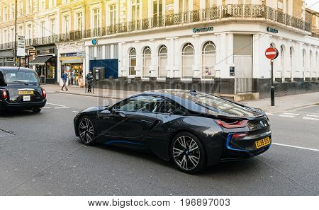 LONDON UNITED KINGDOM - MAR 9 2017: Luxury BMW i8 hybrid electric coupe luxury car driving on the streets of London with hackney carriage car in front and Barclays car in the background. The BMW i8 is a plug-in hybrid sports car developed by BMW.
