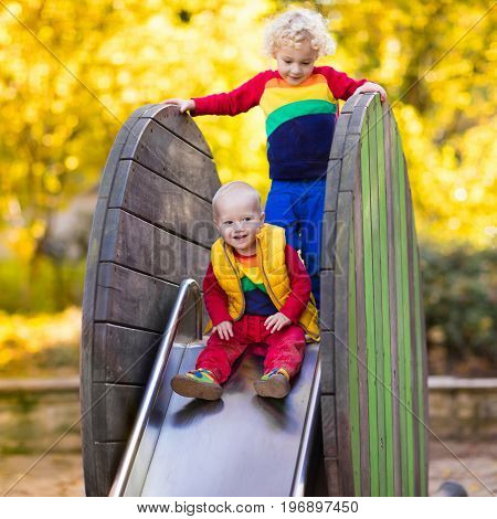 Kids on playground Children play in autumn park. Child on slide and swing on sunny fall day. Preschool or kindergarten yard. Daycare for young kid. Baby on play ground. Outdoor fun in autumn.