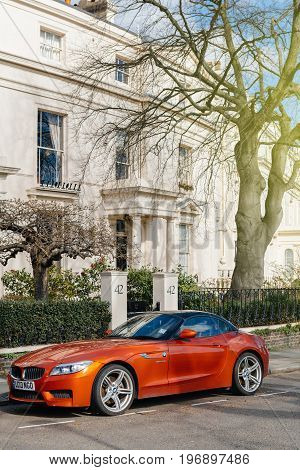 LONDON UNITED KINGDOM - MAR 9 2017: Luxury red BMW Z4 parked in front of luxury mansion in London in expensive neighborhood on a warm summer day. Z4 rear-wheel drive sports car by the German car maker BMW.