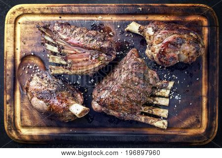 Barbecue Leg of Lamb and Veal Loin as top view on burnt cutting board