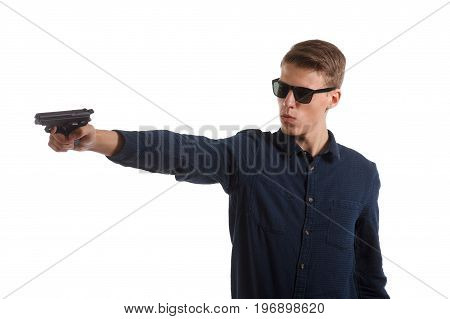 A young man wearing sunglasses and holding a handgun