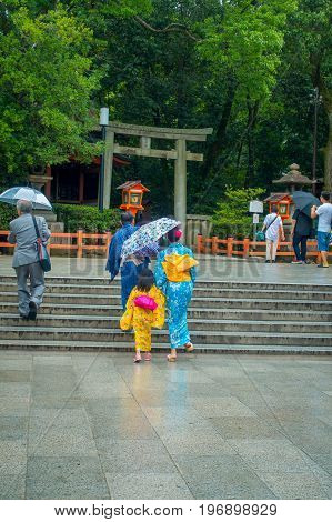 KYOTO, JAPAN - JULY 05, 2017: Young Japanese women wearing traditional Kimono and holding umbrellas in their hands in the Gion district of Kyoto, Gion is Kyoto's most famous geisha district.