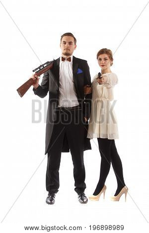 A couple wearing fancy clothes and holding guns