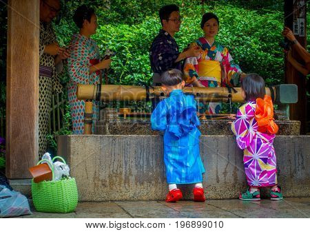 KYOTO, JAPAN - JULY 05, 2017: Young Japanese people wearing traditional Kimono and holding umbrellas in their hands in the Gion district of Kyoto, Gion is Kyoto's most famous geisha district.
