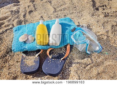 The summer skin care kit, beach towel, flip flop and snorkel on the beach sand