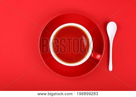Full Cup Of Black Tea Over Red Background