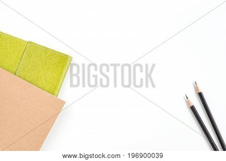 Recycled notebook in green and brown color and two black pencils over white background with copy space for text insertion or decoration