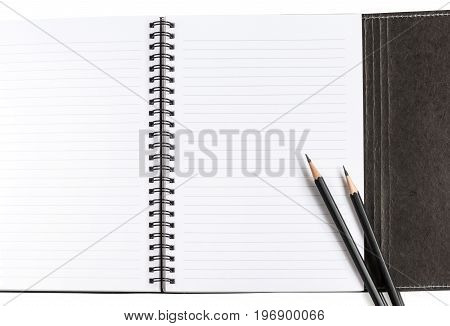Notebook clean blank white paper with lines and black cover and two black pencils on white background for text decoration or insertion