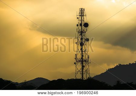 Silhouette of a telecommunication towers with rays of light through the clouds in the sky after the storm