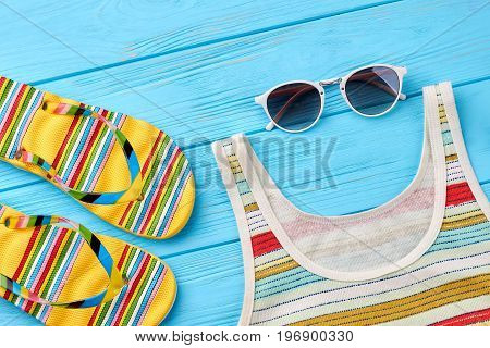 Feminine summer background. Striped slippers and shirt, sunglasses, blue wooden background.