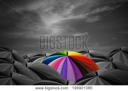 Rainbow umbrella are in a black umbrellas on storm sky background