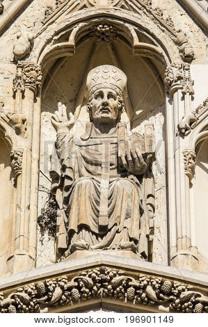 A stone sculpture of the Archbishop of York on the exterior of the Western facade of York Minster in York UK.