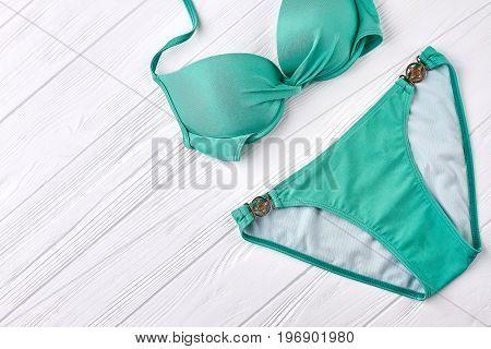 Fashionable women swimsuit. Bathing costume on wooden background.