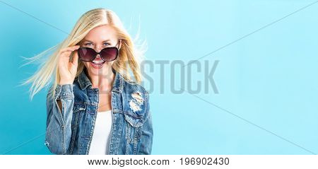 Young woman with sunglasses on a blue background