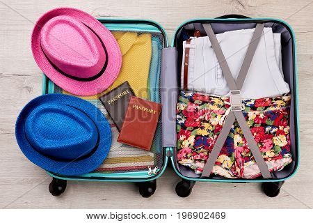 Packed suitcase, hats, passports. Full luggage for summer travelling abroad.