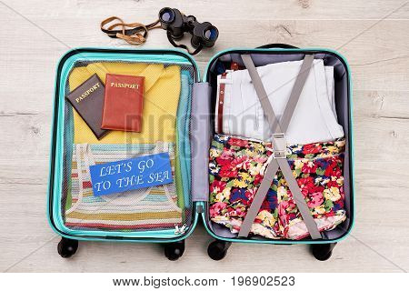 Binocular, full suitcase, wooden background. Accessories for summer vacation of dream.